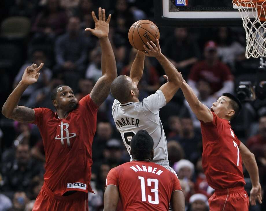 Spurs guard Tony Parker shoots between Rockets guard Jeremy Lin, right, forward Terrence Jones, left, and guard James Harden during the second half. Photo: Darren Abate, Associated Press