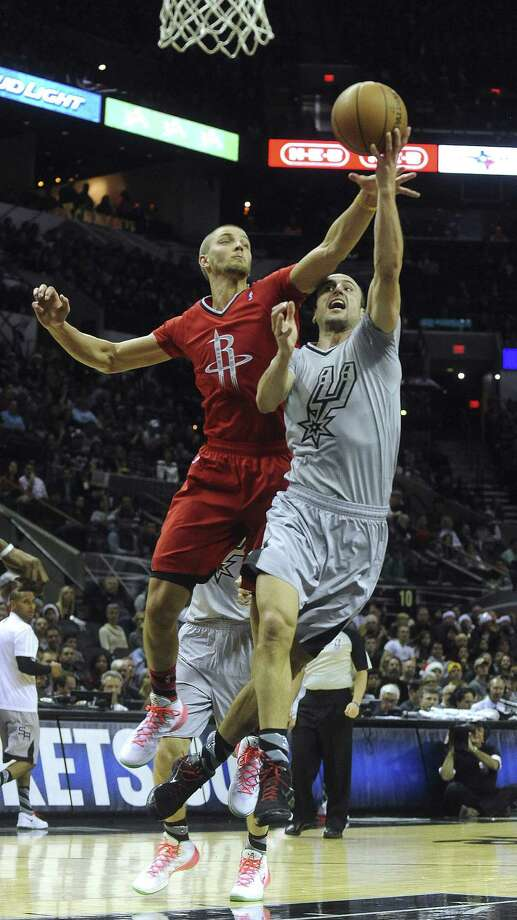 Manu Ginobili (right), drawing a foul from Houston's Chandler Parsons during Wednesday's game at the AT&T Center, led the Spurs with 22 points in defeat. Photo: Billy Calzada / San Antonio Express-News / San Antonio Express-News