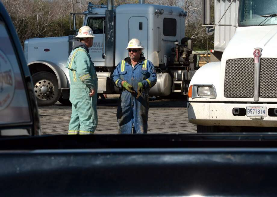 Two workers collaborate at the Spindletop reservoir's newest drill site on Monday. The site is located less than a mile from the 1901 oil gusher that kick started the oil industry. Photo: Guiseppe Barranco, Houston Chronicle