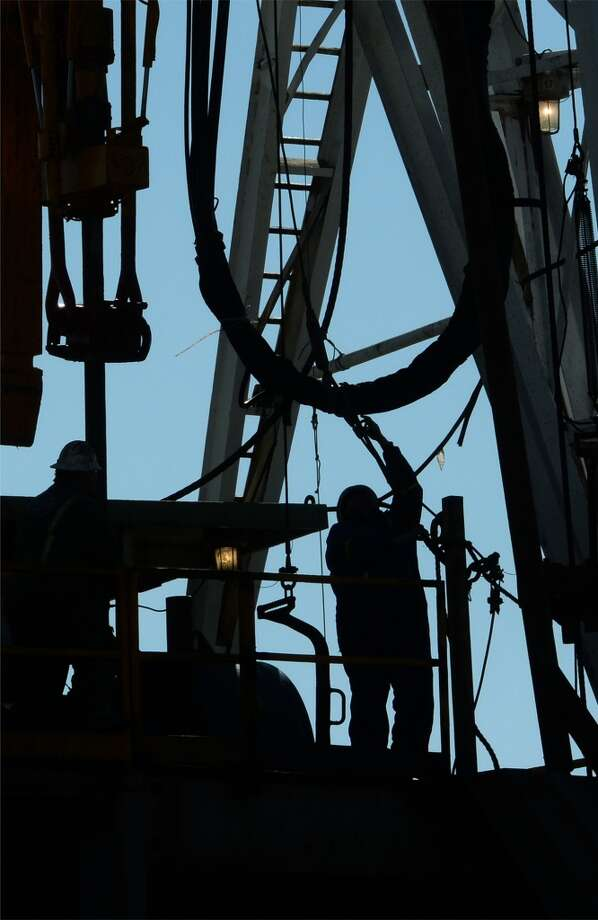 A worker connects drill pipe on a newly operational oil derrick at the Spindletop reservoir on Monday. The site is located less than a mile from the 1901 oil find that kick started the oil industry. Photo: Guiseppe Barranco, Houston Chronicle