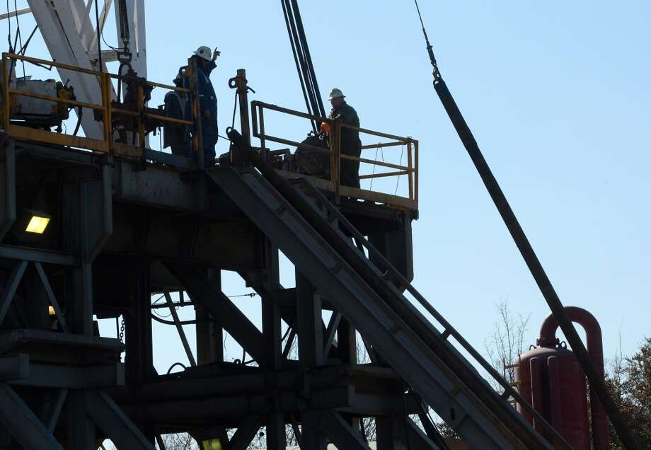 Workers connect drill pipes on a newly operational oil derrick at the Spindletop reservoir on Monday. The site is located less than a mile from the 1901 oil find that kick started the oil industry. Photo: Guiseppe Barranco, Houston Chronicle