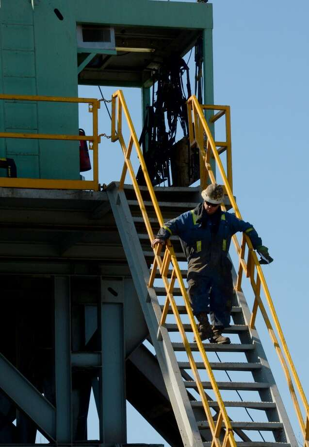 A worker traverses the oil derrick at the Spindletop reservoir's newly operational drilling site on Monday. Photo: Guiseppe Barranco, Houston Chronicle