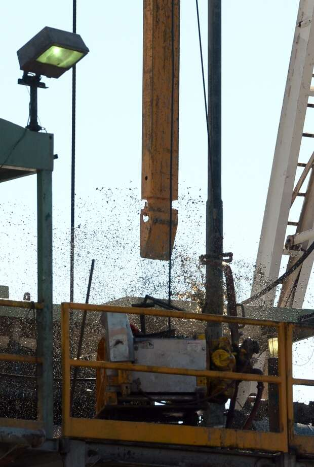 Mud shoots out of the newly dug drilling hole at the Spindletop reservoir while workers add drilling pipes to the derrick on Monday. Photo: Guiseppe Barranco, Houston Chronicle