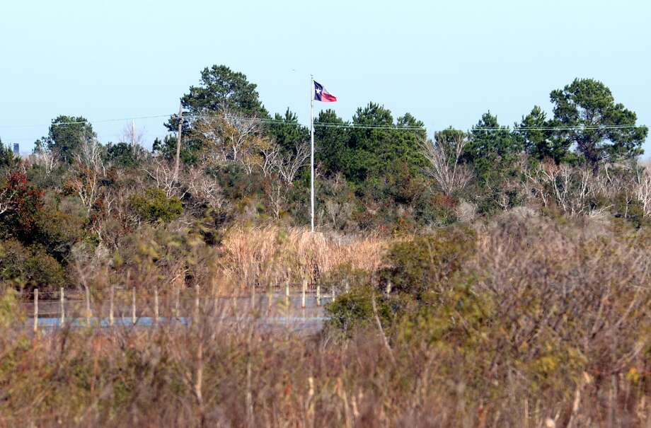 A Texas flag flies over the location of the original Spindletop oil gusher. The famous 1901 oil boom was the first major find of crude. Photo: Guiseppe Barranco, Houston Chronicle