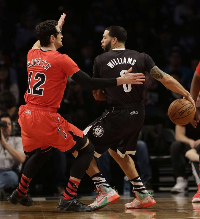 Nets guard Deron Williams, right, passes behind his back while Bulls guard Kirk Hinrich defends during the first half. Photo: Seth Wenig, Associated Press