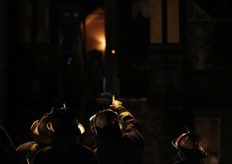 A firefighter points to a charred residence while talking with other firefighters December 25, 2013 outside of a home that caught fire Christmas night, injuring two men on 618 Baker Street in San Francisco, Calif. Photo: Leah Millis, The Chronicle