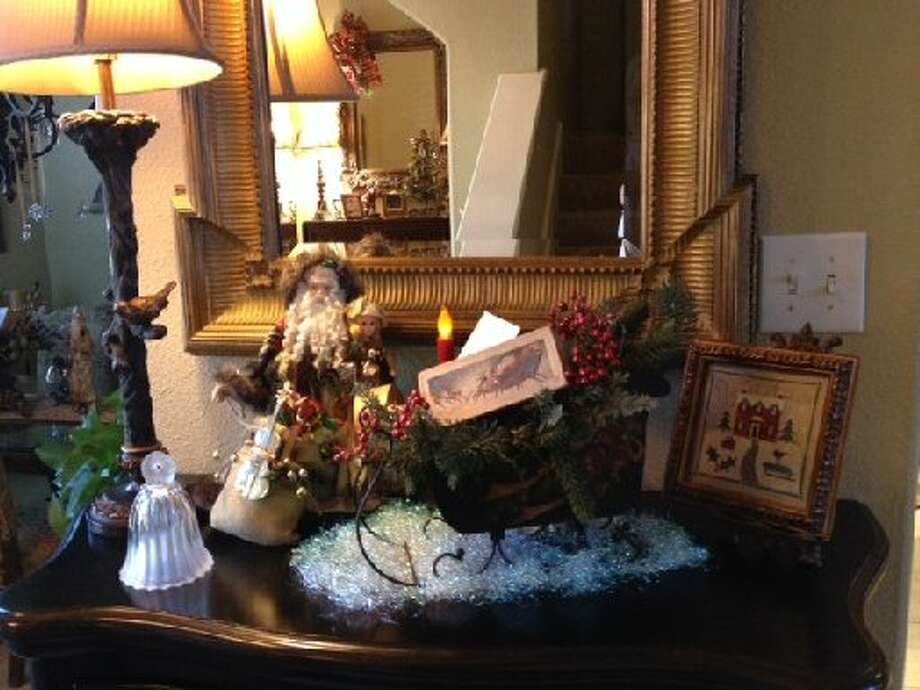"Diane Simpson: ""This vignette is on our entry chest. It features a Santa with a robe made from an old quilt and mink with a bag of vintage toys. I got this at a craft show in 1993. The sleigh is also old."" Photo: Courtesy Photo"