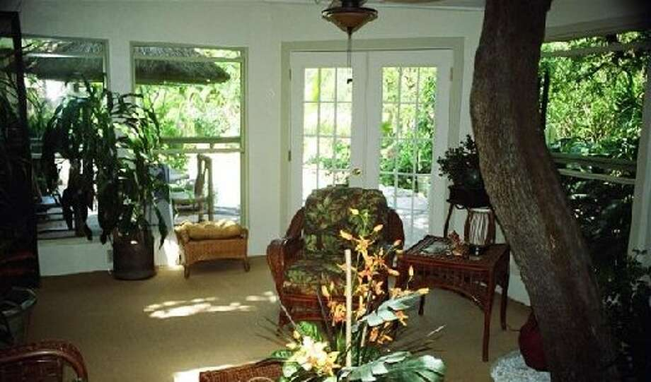 "Gerald and Donna Anglin: ""Please note tree growing in porch. This time of year we have to move a number of plants into the porch/sunroom/Florida room. Truth is we have never come up with a good name to describe this addition. The outside area around the room is planted to that the view is green all year around. Much tropical vegetation."" Photo: Courtesy Photo"