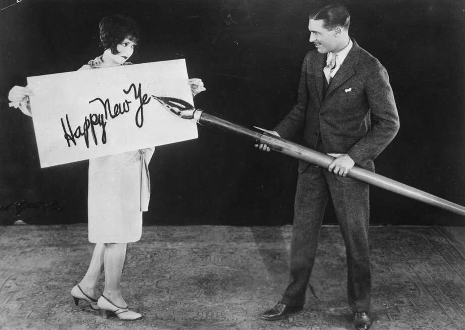 American actress Clara Bow holds up a large card while actor Larry Gray inscribes a New Year's greeting with a giant pen, circa 1925. Photo: General Photographic Agency, Getty Images / Hulton Archive