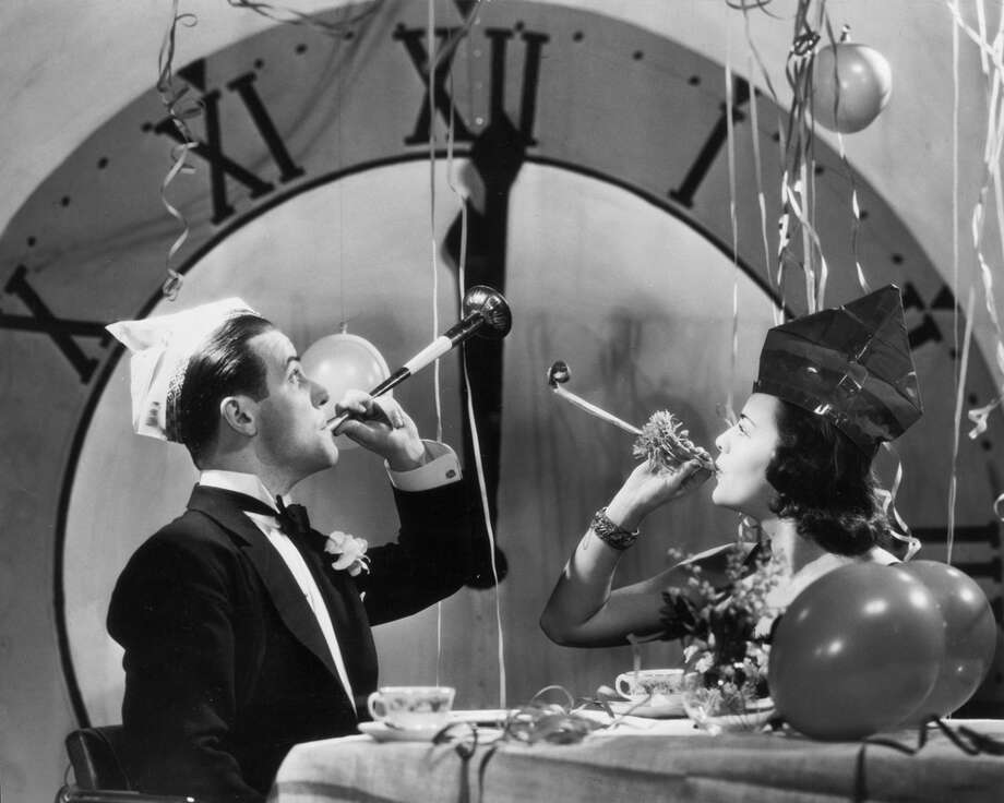 A couple rings in the New Year with party blowers and streamers, circa 1930. Photo: FPG, Getty Images / 2004 Getty Images