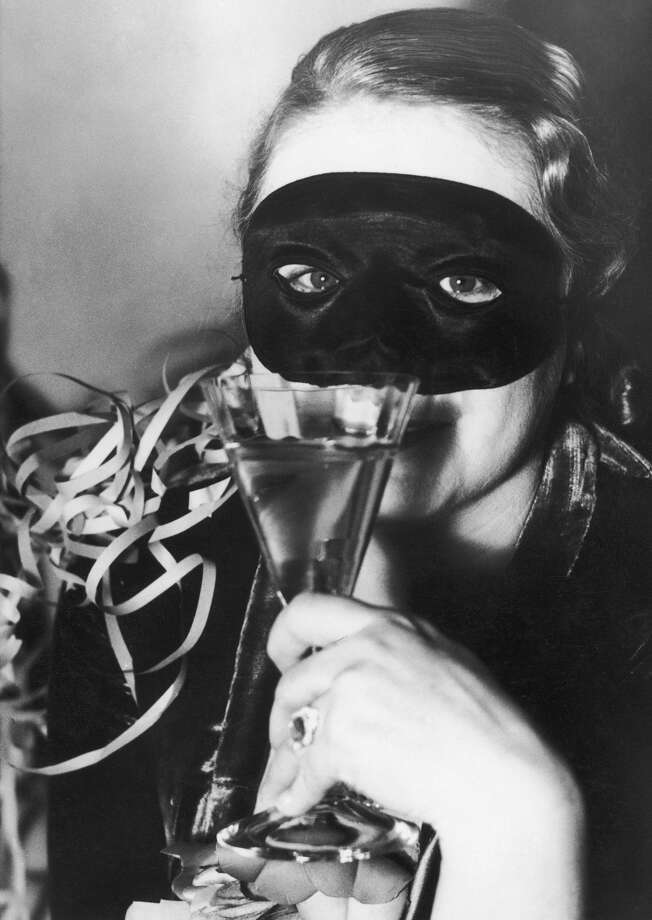An unidentified woman in a mask holds a cocktail glass at a New Year's Eve party, circa 1930. Photo: Mansell, Getty Images / Time & Life Pictures