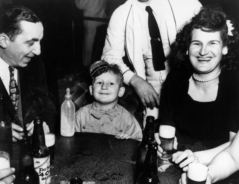 A three-year-old boy accompanies his parents to a New York nightclub to celebrate New Year's Eve on Jan. 1, 1943. At five in the morning, he is still welcoming in the New Year with a bottle of milk. Photo: Weegee(Arthur Fellig)/Internatio, Getty Images / ICP