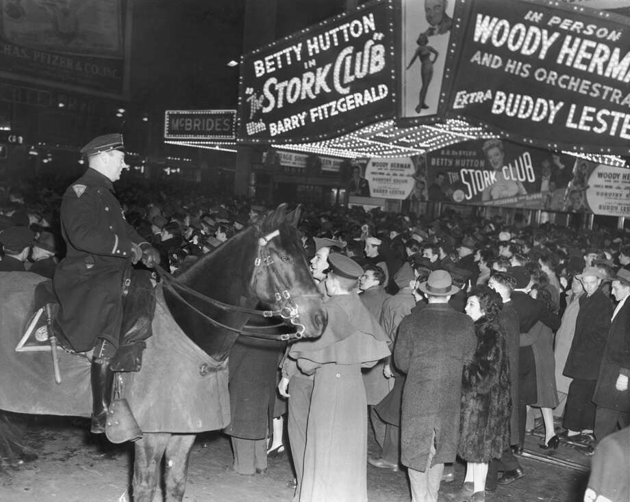 "Crowds gather under a marquee advertising director Hal Walker's film, ""The Stork Club,"" at night on Broadway in Times Square, New York City, New Year's Eve on Dec. 31, 1945. A mounted police officer laughs in the foreground. Photo: Lawrence Thornton, Getty Images / Archive Photos"