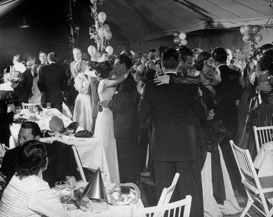 Charles Russell kisses his wife at the stroke of midnight during Samuel Spiegel's New Year's Eve party on Dec. 31, 1948. Photo: Peter Stackpole, Getty Images / Time Life Pictures