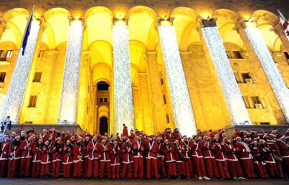 People dressed as Santa Claus perform near a New Year tree in front of the parliament building in Tbilisi, late on December 25, 2013. Orthodox Christians in Georgia celebrate Christmas on January 7. Photo: Vano Shlamov, AFP/Getty Images