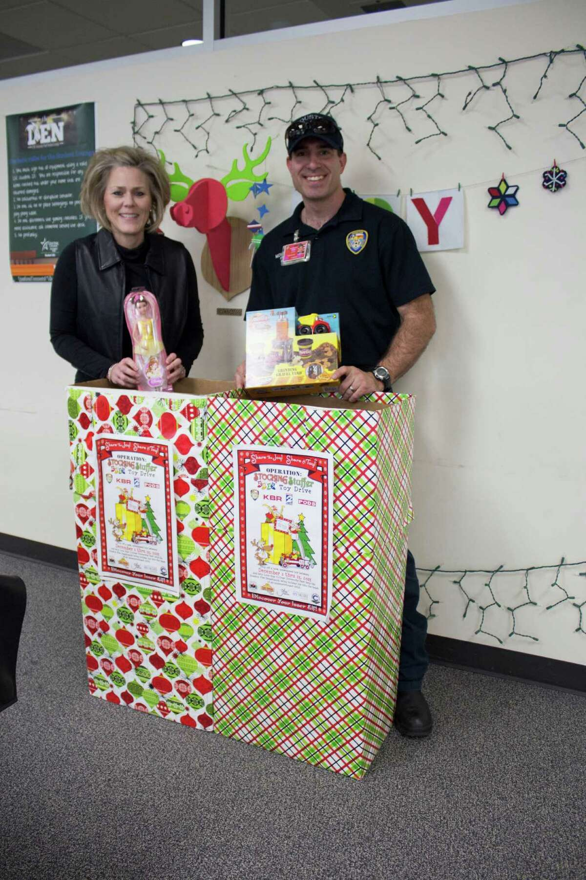From left, Janice Straker of Lone Star College University Park and Mike Spratt of the Houston Fire Department show toys collected during Operation Stocking Stuffer.