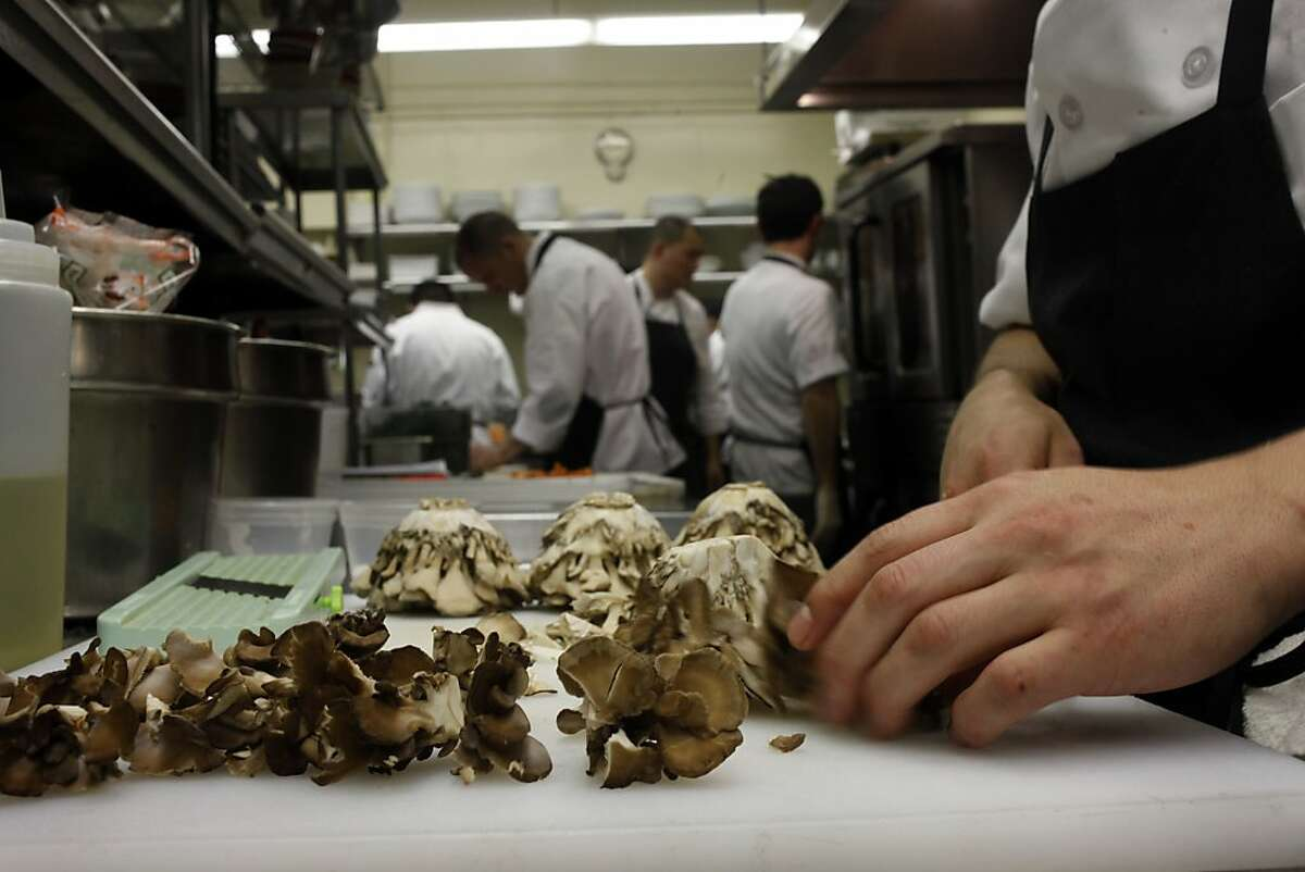 Line cook Silver Garcia prepares mushrooms for a dish for Friday nights dinner, December 20, 2013, at the Aziza Restaurant in San Francisco, Calif.