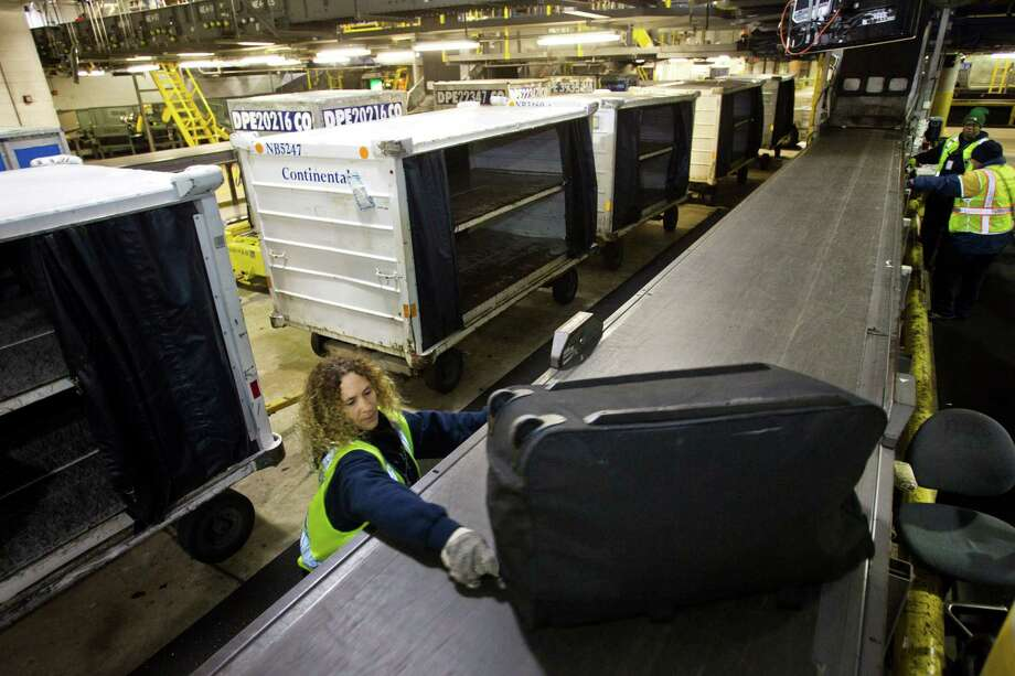 Mary Turton reaches for one of thousands of bags that move through Bush Intercontinental's luggage system each day. Photo: Brett Coomer, Staff / © 2013 Houston Chronicle