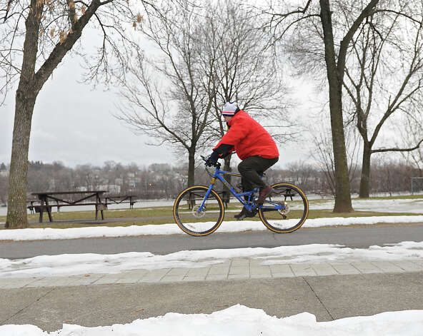 A man braves the cold as he rides his bike along the Corning Preserve path on Thursday, Dec. 26, 2013 in Albany, N.Y. (Lori Van Buren / Times Union) Photo: Lori Van Buren / 00025157A