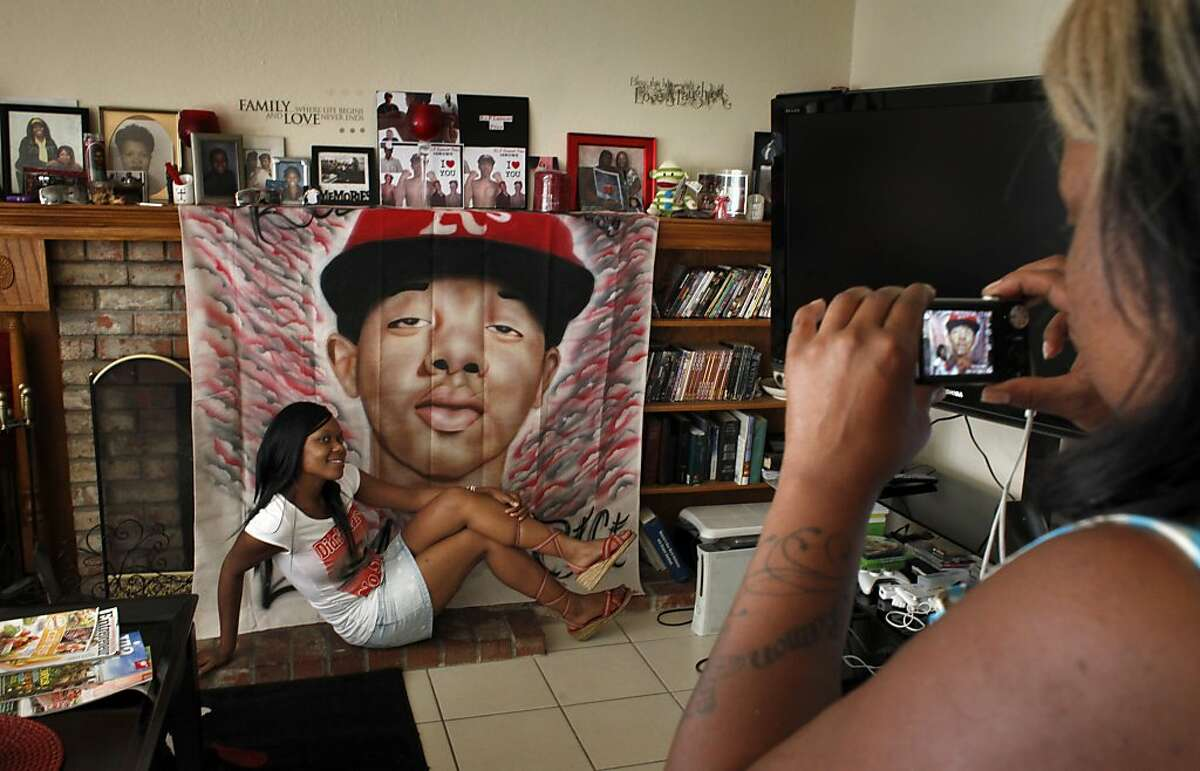 Karlisha Ely, left, poses as Nicole Hodge takes a picture of her with the banner of Lamont Price to commemorate his birthday, Wednesday July 4, 2012, in Antioch, Calif. Photo: Lacy Atkins, The Chronicle