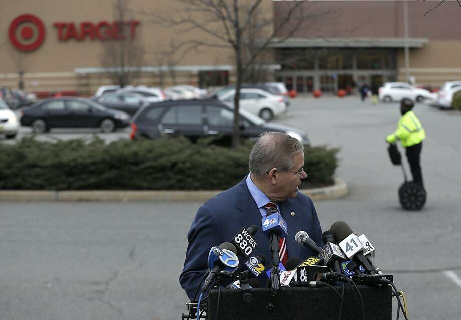 A security guard rides by on a personal moving device as U.S. Sen. Robert Menendez looks back during a news conference outside of a Target store, Thursday, Dec. 26, 2013, in Jersey City, N.J. Menendez, a member of the Senate banking committee, is laying out efforts to protect consumers' personal information, in light news that information from 40 million Target customers were stolen. (AP Photo/Julio Cortez) Photo: Julio Cortez, Associated Press