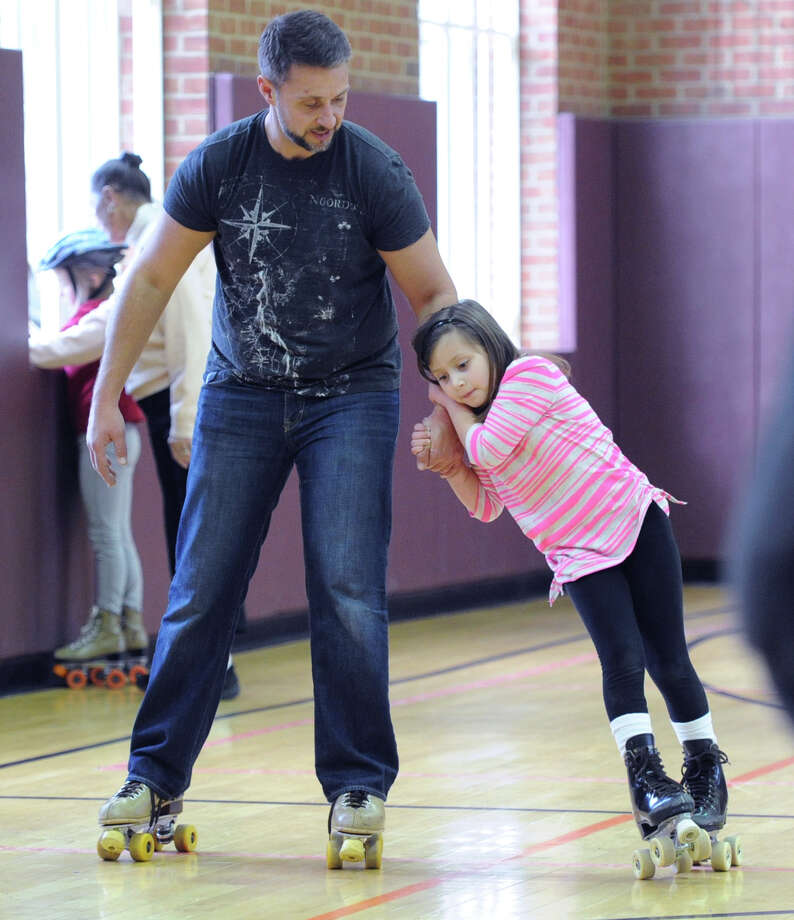 Cristina DeBlasio, 6, of Greenwich, holds onto the arm of her father, Rich DeBlasio of Greenwich, during the Greenwich Department of Parks and Recreation's Roller Skating Party at the Western Greenwich Civic Center in Glenville, Thursday, Dec. 26, 2013. Photo: Bob Luckey / Greenwich Time