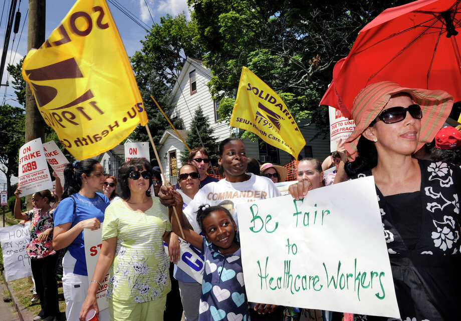 In this file photo, nursing home workers walked off their jobs at Danbury Health Care Center on Tuesday, July 3, 2012, in protest of labor concessions made by HealthBridge, the New Jersey-based company that owns the facility. Jasmine Brown, 8, holds a sign while joining her mother Charlotte Abraham on the picket line in front  of Danbury Health Care on Osborne Street in Danbury. Abraham, a former employee of the company, was there in support of her former co-workers. Photo: Carol Kaliff / The News-Times