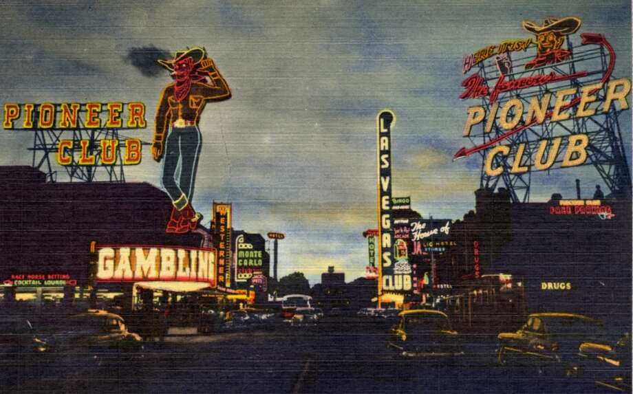 Vintage linen postcard from 1956 showing the Howdy Podner sign, the largest mechanical sign in the world at the time. The sign lights up the night sky over a view of Fremont Street and other establishments. Photo: Curt Teich Postcard Archives, Getty Images