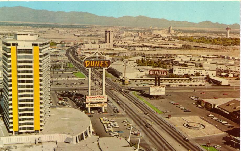 "A vintage postcard showing a bird's eye view of the Dunes hotel and the Las Vegas Strip in 1967. The Dunes started at a disadvantage due to its location at the far end of the Strip. The casino closed a year after opening until Jake Gottlieb and Major Riddle bought the vacant casino in 1956. Unfortunately, the two had worked closely with the ""Chicago Outfit,"" a well known crime syndicate. They eventually brought about the first topless show to the Strip. Photo: Curt Teich Postcard Archives, Getty Images"