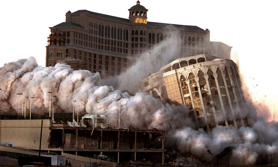 The Aladdin Hotel and Casino in Las Vegas, NV, implodes with explosive charges in 1998, to make way for the Bellagio Hotel(rear), which was under construction at the time. The Aladdin Hotel was and built in 1966 was replaced with the 1.3 billion USD Bellagio Hotel, which planned to open in Spring 2000. Photo: JOHN GURZINSKI, AFP/Getty Images