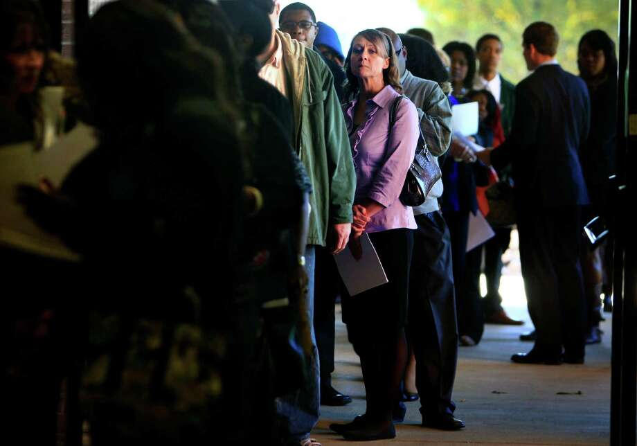 FILE - In this Nov. 7, 2013 file photo, Jona Caldwell joins a long line of job seekers outside the Ferguson Community Center in Cordova, Tenn. The Labor Department reports on the number of Americans who applied for unemployment benefits in the last week on Dec. 26, 2013. (AP Photo/The Commercial Appeal, Jim Weber, File) ORG XMIT: TNMEM202 Photo: Jim Weber / The Commercial Appeal
