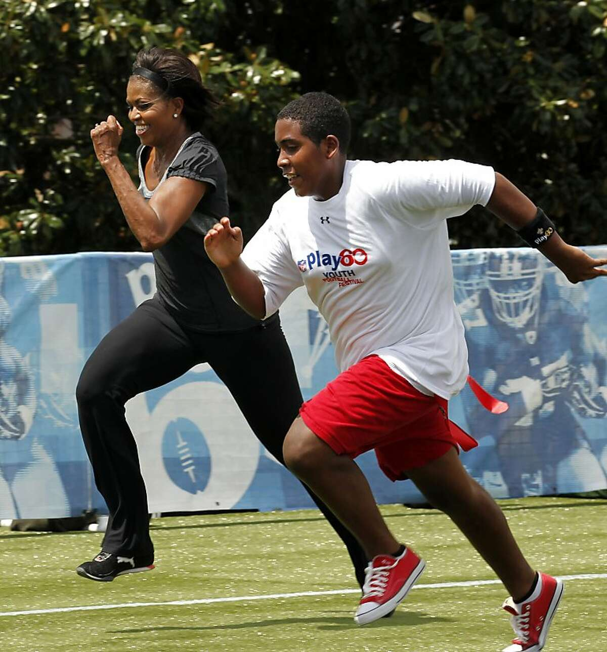 FILE - In this Sept. 8, 2010, file photo, first lady Michelle Obama runs a 40-yard sprint during the Let's Move! Campaign and the NFL's Play 60 Campaign festivities with area youth, to promote exercise and fight childhood obesity, in New Orleans. Recent changes put in place by the food industry are in response to the campaign against childhood obesity that Obama began waging three years ago. (AP Photo/Gerald Herbert, file)
