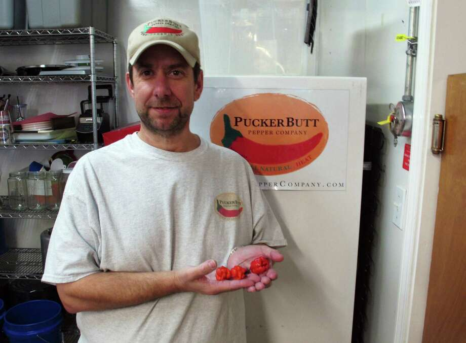Ed Currie holds Carolina Reaper peppers in Fort Mill, S.C. Last month, Guinness World Records decided Currie's peppers were the hottest on Earth. Photo: Jeffrey Collins / Associated Press / AP