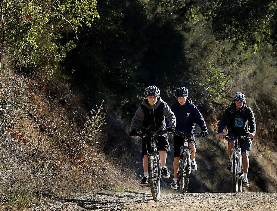 With 8-year-old Ari Kaufman leading the way, Ryan Loften (right) guides children with their mountain biking skills on a ride near Phoenix Lake in Ross. Loften teaches youths of all ages to ride in the Mt. Tam Bikes Camp during summer or with after- school lessons. Photo: Brant Ward, The Chronicle