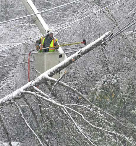 Carl Taylor, an arborist, trims ice-coated tree limbs that became entangled in power lines in Belgrade, Maine. Photo: Michael G. Seamans / Central Maine Morning Sentinel / The Central Maine Morning Sentin