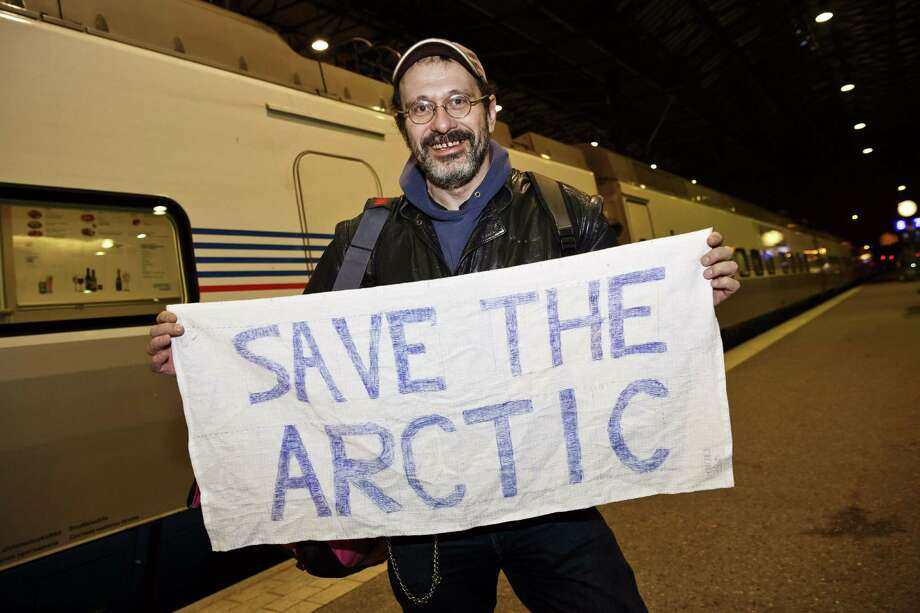 "Greenpeace activist Dmitri Litvinov shows a banner reading ""Save the Arctic"" on arrival at the railway station in Helsinki on December 26, 2013. Dmitri was the first Greenpeace activist on a train out of Russia on December 26, more than three months after he was arrested along with 29 fellow crew members of a ship protesting against Arctic oil drilling. Dmitri Litvinov, a Swedish-American of Russian origin, left Saint Petersburg for Finland's capital Helsinki on a train departing at 8:25 pm (1625 GMT) after Russia issued exit visas for 14 of the crew following a pardon by President Vladimir Putin. AFP PHOTO / LEHTIKUVA / RONI REKOMAA &&& FINLAND OUTRoni Rekomaa/AFP/Getty Images Photo: RONI REKOMAA, Stringer / AFP"