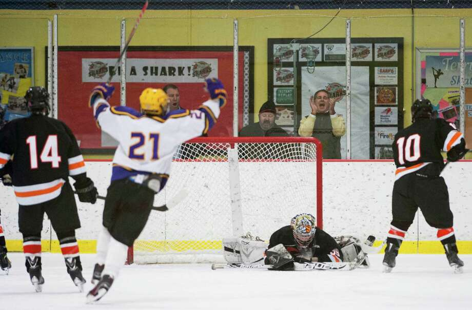 Westhill high school's Max Puk (21) celebrates a goal scored by teammate Scott Reville during a boys ice hockey game against Stamford high school played at Terry Conners Ice Rink, Stamford, CT on Thursday, December, 26th, 2013. Photo: Mark Conrad / Connecticut Post Freelance