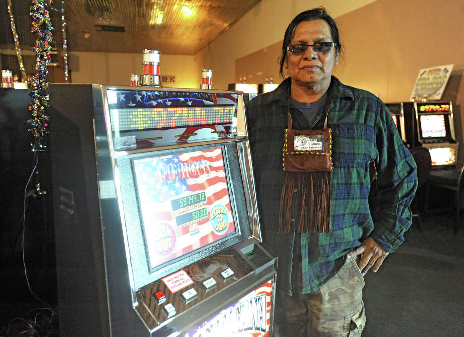 Thomas Square, Wolf Clan Representative of Men's Council, stands by a slot machine at Three feathers Casino on the Akwesasne Reservation Tuesday April 24, 2012 in Hogansburg, N.Y. Square's Mohawk name is Rarahkwisere. This casino is run without  authorization from the St. Regis Mohawk Tribal Council. (Lori Van Buren / Times Union) Photo: Lori Van Buren / 00017339A