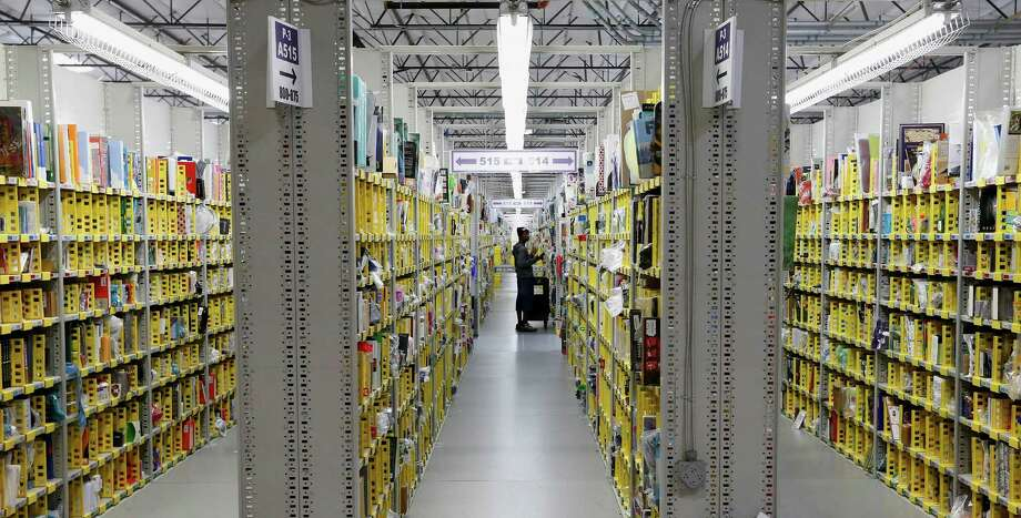 An Amazon.com employee stocks a shelf early this month. Many shoppers waited until the last possible minute to buy presents this year, even online. Photo: Ross D. Franklin, STF / AP