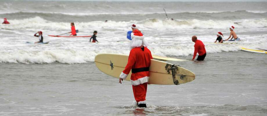 George Trosset, center, prepares to surf as he hosts his 5th Surfing Santas event in Cocoa Beach, Fla., Tuesday, Dec. 24, 2013. The event raised money for the non profit Grind for Life. (AP Photo/Florida Today, Malcolm Denemark) ORG XMIT: FLROC401 Photo: Malcolm Denemark / Florida Today