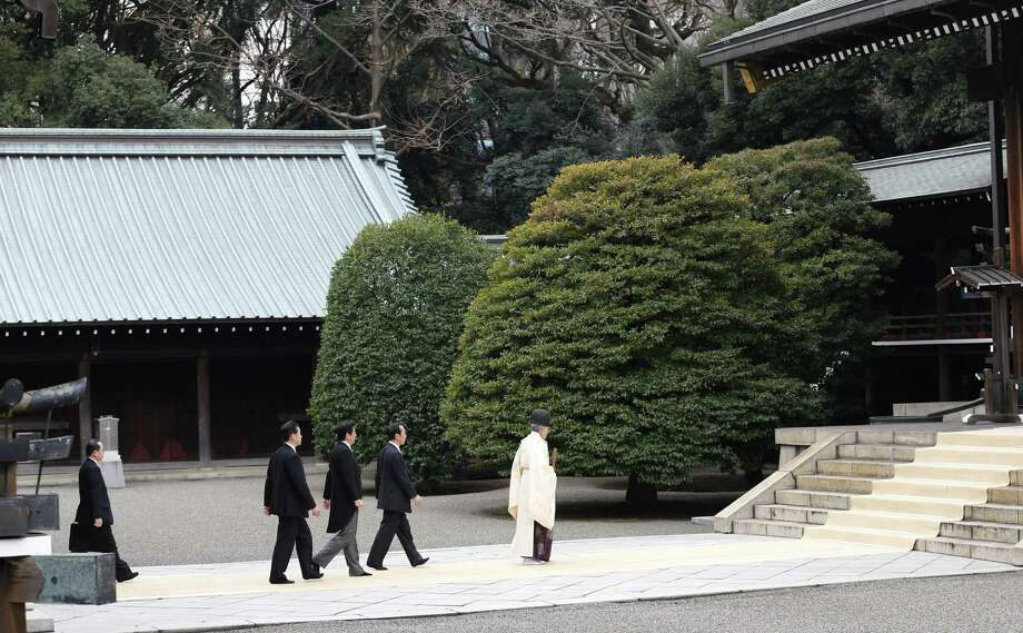 Japanese Prime Minister Shinzo Abe (third from right) follows a Shinto priest to Yasukuni Shrine, which honors Japan's war dead, including 14 war criminals, in Tokyo. Abe's visit infuriated China and South Korea and disappointed the White House. Photo: Shizuo Kambayashi / Associated Press / AP