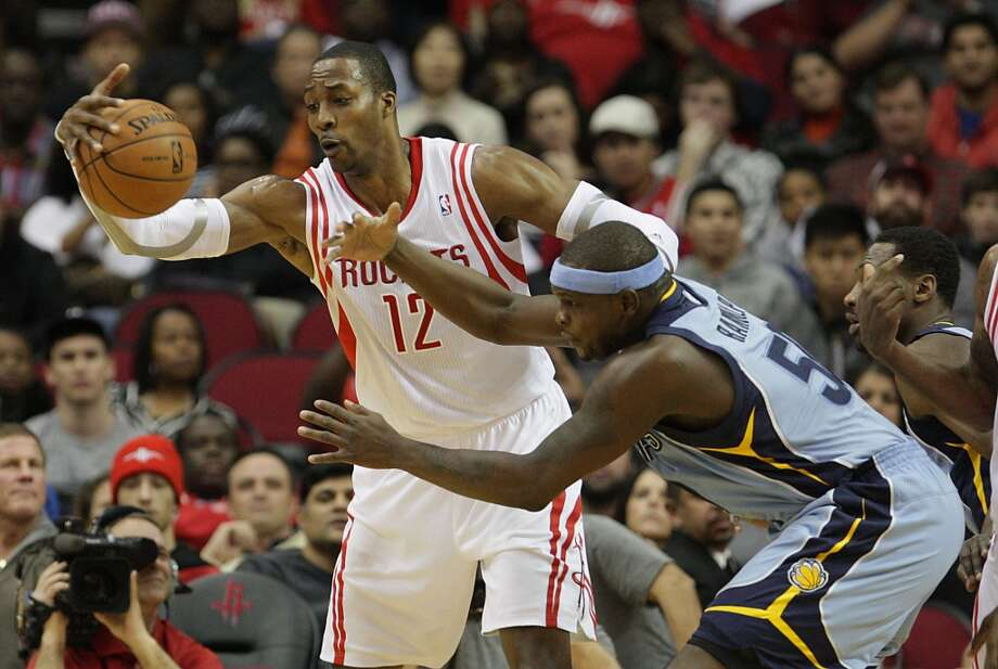 Dec. 26: Rockets 100, Grizzlies 92  Rockets power forward Dwight Howard left, and Grizzlies power forward Zach Randolph right, reach for the ball. Photo: James Nielsen, Houston Chronicle