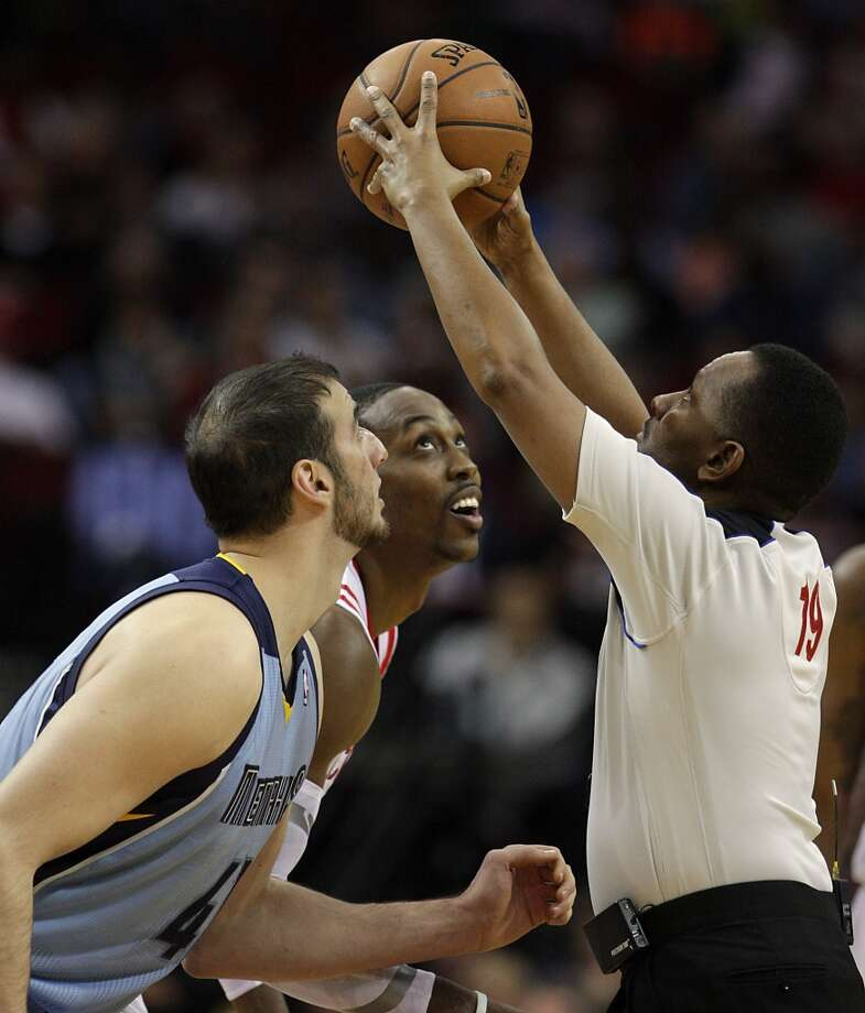 Grizzlies center Kosta Koufos left, Rockets power forward Dwight Howard center, keep their eyes on the ball as NBA official James Capers right, prepares to toss the ball for tip off. Photo: James Nielsen, Houston Chronicle
