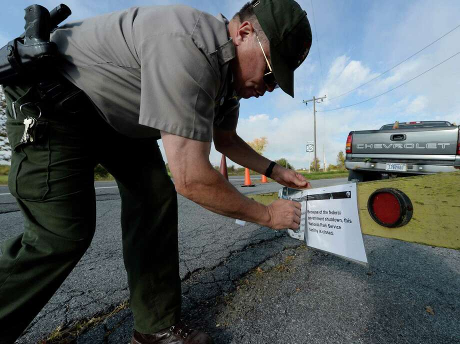 Park ranger Keith Hatfield places a closing notice on a sawhorse at one of the entrances to Saratoga National Historical Park Tuesday morning, Oct. 1, 2013, in Stillwater, N.Y. The park will remain closed until the federal shutdown ends.   (Skip Dickstein/Times Union) Photo: SKIP DICKSTEIN