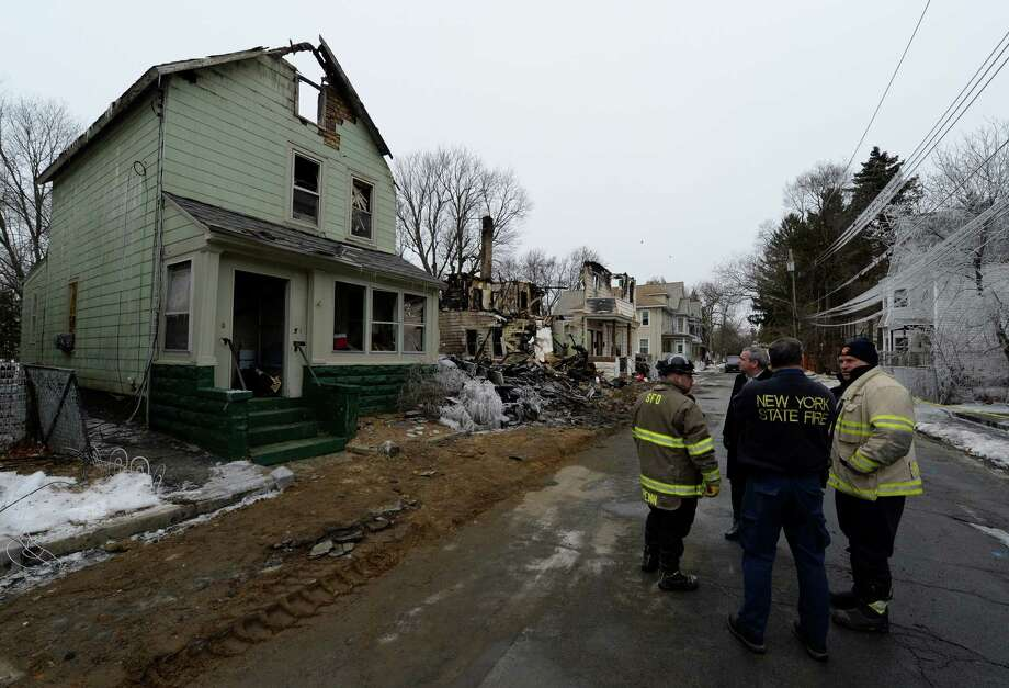 Schenectady Mayor Gary McCarthy, second from left is joined by State and City fire officials as discuss the damage to three buildings on Moyston Street Thursday Dec. 26, 2013, in Schenectady, N.Y.  Wrecking crews were on the way to remove the remains of the buildings damaged by fire on Christmas Eve.        (Skip Dickstein / Times Union) Photo: SKIP DICKSTEIN