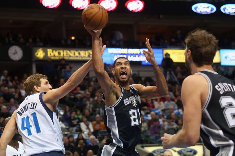 Tim Duncan #21 of the San Antonio Spurs is fouled by Dirk Nowitzki #41 of the Dallas Mavericks in the first quarter at American Airlines Center on December 26, 2013 in Dallas. Photo: Ronald Martinez, Getty Images