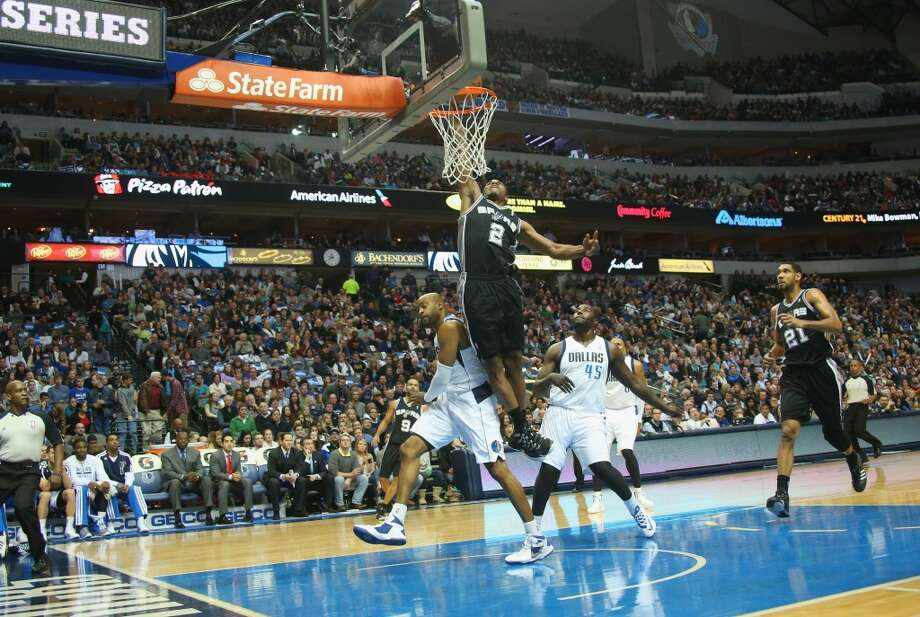 Kawhi Leonard #2 of the San Antonio Spurs makes a layup against Vince Carter #25 and DeJuan Blair #45 of the Dallas Mavericks at American Airlines Center on December 26, 2013 in Dallas. Photo: Ronald Martinez, Getty Images