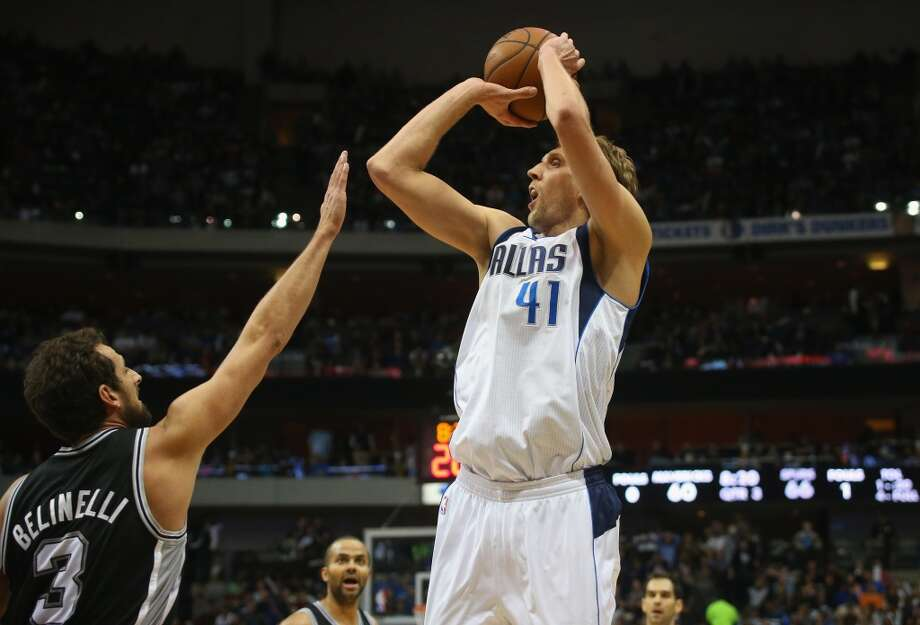 Dirk Nowitzki #41 of the Dallas Mavericks takes a shot against Marco Belinelli #3 of the San Antonio Spurs at American Airlines Center on December 26, 2013 in Dallas. Photo: Ronald Martinez, Getty Images