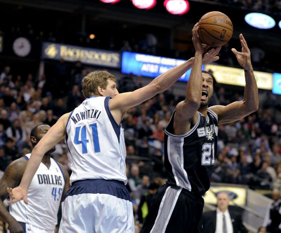 Dallas Mavericks forward Dirk Nowitzki (41) defends a shot by San Antonio Spurs forward Tim Duncan (21) during the first half of an NBA basketball game, Thursday, Dec. 26, 2013, in Dallas. Photo: Matt Strasen, Associated Press