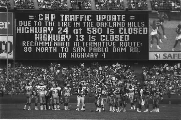 A photograph shows the scoreboarad at Candlestick Park on October 20, 1991, warning fans of road closures due to the Oakland Hills Fire.